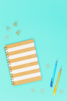 Flat lay with stationery for school, education. closed notebook on spring, pencil, golden metal clips for paper.