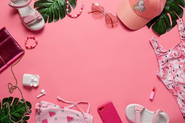 夏のアクセサリーを備えたフラットレイ。子供服やアクセサリー、電話、ヘッドフォン、口紅、ピンクの背景に緑の葉。フラットレイ。