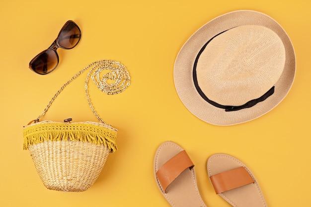 女性のための夏のアクセサリーとフラットレイ。日よけ帽、サングラス、ビーチサンダル、バッグ。夏の旅行、休暇、熱保護の概念。コピースペース、上面図