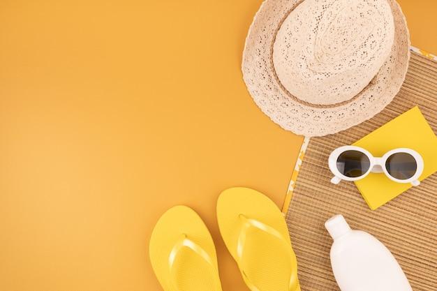 女性のための夏のアクセサリーとフラットレイ。日よけ帽、サングラス、日焼け止め保護、ビーチサンダル、バッグ。夏の旅行、休暇、熱保護の概念。コピースペース、上面図