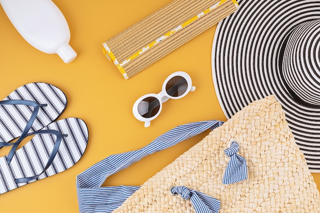 Flat lay with summer accessories for woman. sun hat, sunglasses, sunscreen protection, flip flops and bag. summer travel, vacations, heat protection concept. copy space, top view