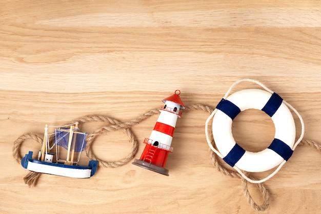 海側のシンボルで夏休みとフラットレイ。灯台、ボート、セーラーロープ。コピースペース、上面図 Premium写真