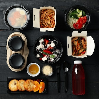 Flat lay with takeaway food on wooden background. food delivery