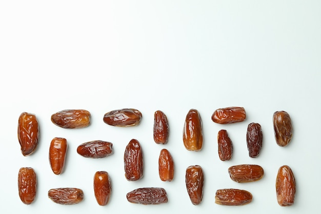 Flat lay with tasty dates on white background, space for text