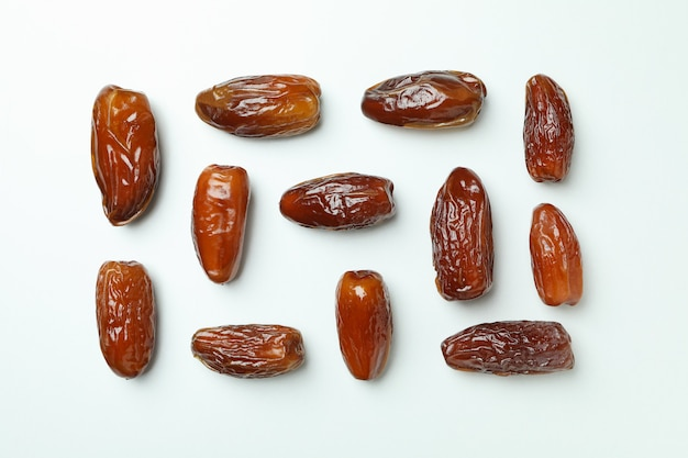 Flat lay with tasty dates on white background