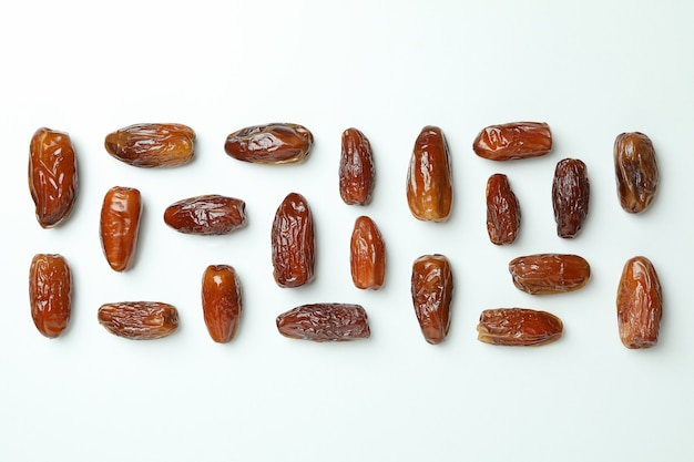 Flat lay with tasty dates on white