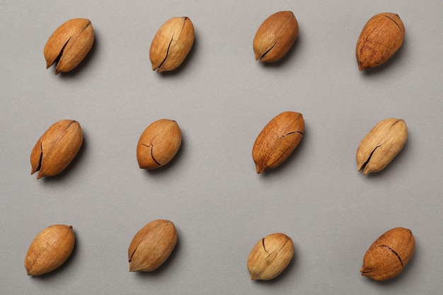 Flat lay with tasty pecan nuts on gray wall