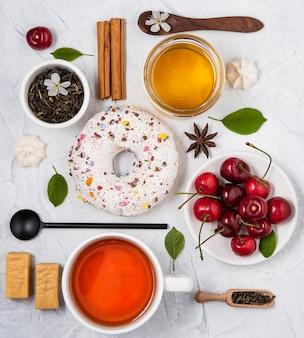 フラットは、白いテーブルトップビューに紅茶ドーナツ蜂蜜チェリースプーン朝食組成物を置く