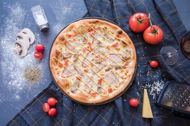 Flat lay with traditional italian pizza on dark blue stone table and various ingredients