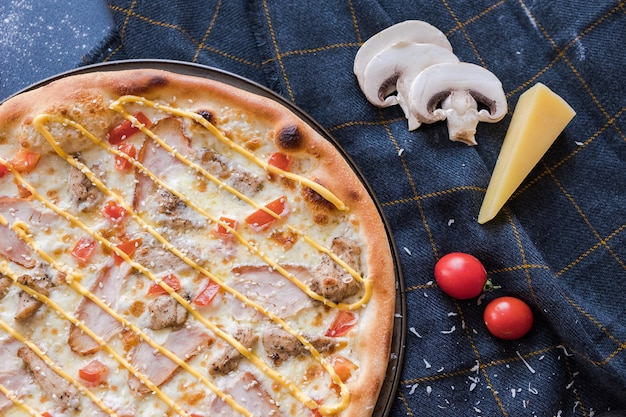 Flat lay with traditional italian pizza with chiken on dark blue stone table