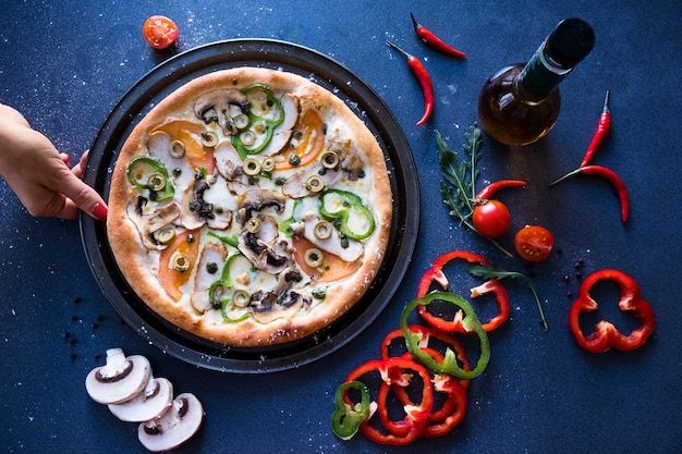 Flat lay with traditional italian pizza with mushrooms, pepper and tomatoes on dark blue stone table