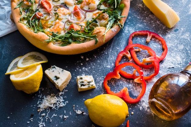 Flat lay with traditional italian pizza with shrimp, mozzarella and arugula