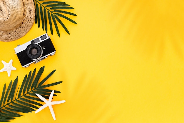 Flat lay with traveler accessories: tropical palm leaf, retro camera, sun hat,  starfish on yellow background