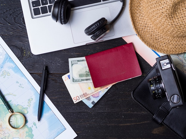 Flat lay with travelling accessories on wooden surface
