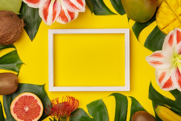 Flat lay with tropical fruits, plants and photo frame background