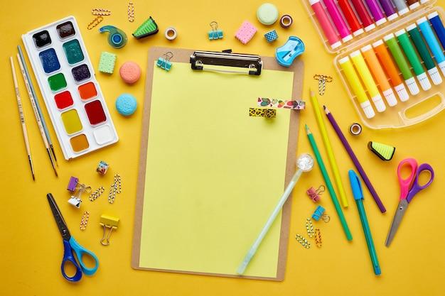黄色のさまざまなカラフルな学用品とフラットレイ