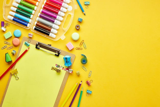 Flat lay with various colorful school supplies on yellow