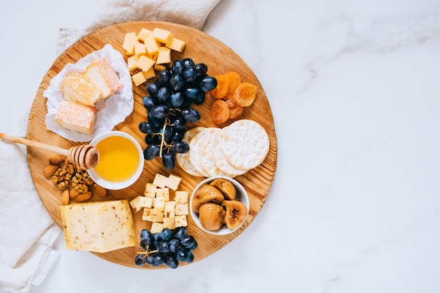 Flat lay with various types of cheese, grapes, nuts, honey and cracker in wooden board on marble