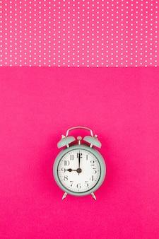水玉模様のパステルカラーの背景の上にヴィンテージの目覚まし時計でフラットレイ