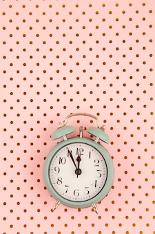 ピンクのパステルカラーの背景の上にヴィンテージの目覚まし時計とフラットレイ