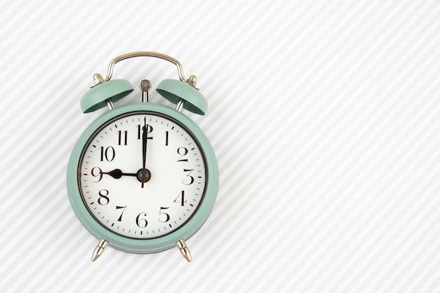 縞模様の背景の上にヴィンテージの目覚まし時計とフラットレイ