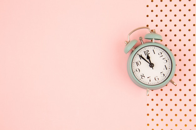 Flat lay with vintage alarm clock over pastel background