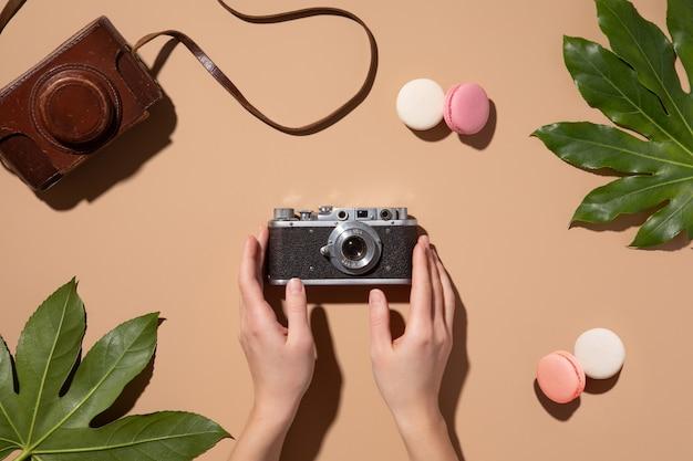 ベージュの背景にビンテージ写真カメラでフラットレイ。トップビューオフィステーブルデスク。ファッションの女の子のアクセサリー、旅行の背景。