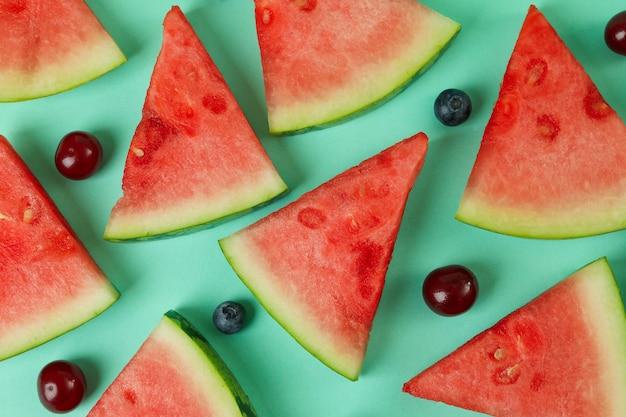 Плоская планировка с ломтиками арбуза и ягодами на мятном фоне