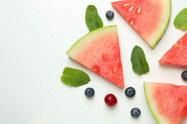 Плоская планировка с ломтиками арбуза и ягодами на белом фоне