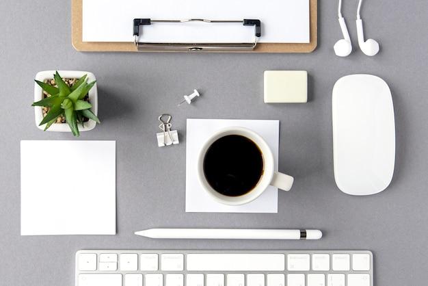 흰색 최소한의 구성으로 평평한 평지. 비즈니스 직장입니다. 키보드, 빈 시트, 펜, 헤드폰, 식물, 밝은 회색 표면에 있는 커피 컵을 모형으로. 평면도.