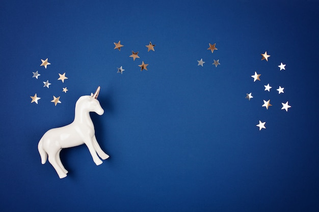 Flat lay with white unicorn and stars over the blue background
