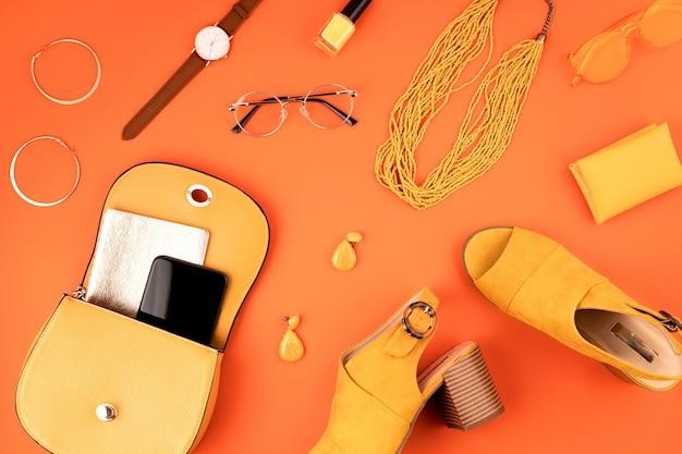 Квартира лежала с женскими модными аксессуарами желтого цвета над оранжевой кожаной текстурированной стеной. мода, онлайн-блог о красоте, летний стиль, шоппинг и концепция тенденций