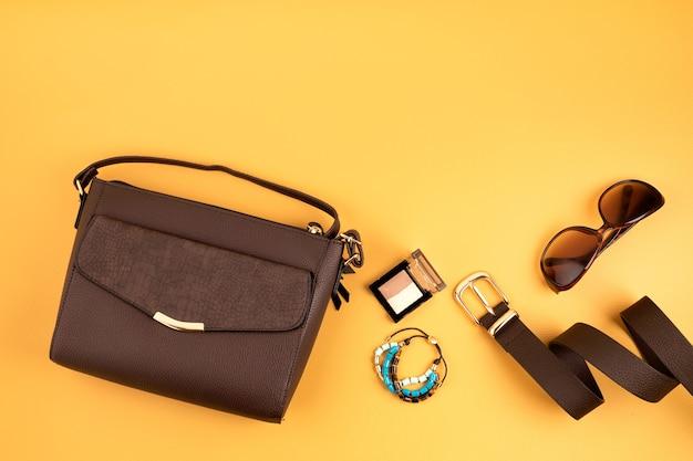 노란색 벽에 여자 패션 액세서리와 함께 플랫 누워. 패션, 온라인 뷰티 블로그, 여름 스타일, 쇼핑 및 트렌드 개념. 평면도
