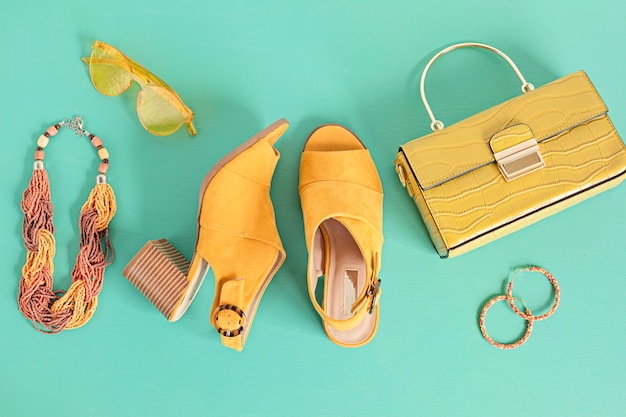 Flat lay with woman fashion accessories in yellow color over turquoise wall. fashion, online beauty blog, summer style, shopping and trends concept