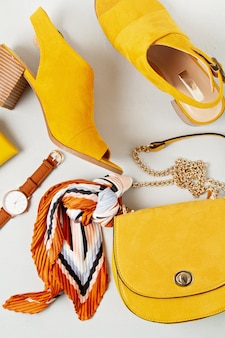 Flat lay with woman fashion accessories in yellow colors
