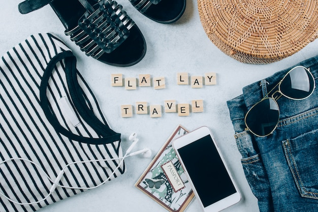 Flat lay with women's clothing and accessories. striped t-shirt, shorts, fashionable rattan bag.