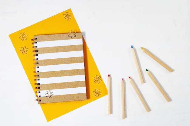 Flat lay with wooden colored pencils, fashion copybook for writing and drawing on tabletop work space with copy space. painting supplies. top view.