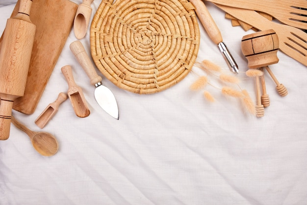 Flat lay with wooden kitchen utensils, cooking tools on textile background, ktchenware collection captured from above, mockup, frame.
