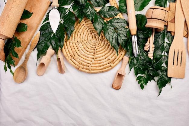 緑の葉が付いた木製の台所用品、テキスタイルの背景に調理器具、料理ブログとクラスのコンセプト、上からキャプチャされたktchenwareコレクション、モックアップ、フレームを備えたフラットレイ