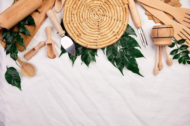 緑の葉と木製の台所用品、テキスタイルの調理器具を備えたフラットレイ