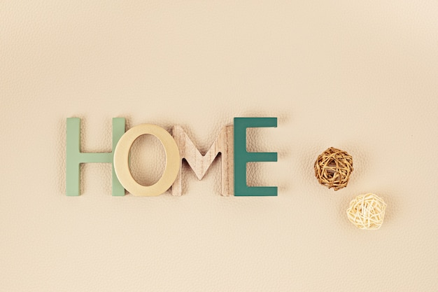 革の質感のあるニュートラルなベージュの壁の上に、木製の単語が家にあるフラットレイ。家の快適さ、装飾の最小限の概念。上面図、コピースペース