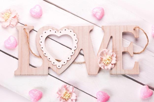 Плоская планировка с деревянным словом любви, розовыми сердцами и цветами.
