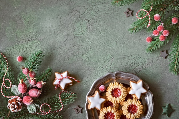 Flat lay with xmas decorations in green and red with frosted berries, trinkets and christmas cookies
