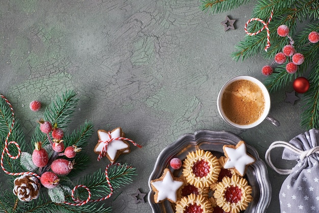 Flat lay with xmas decorations in green and red with frosted berries and trinkets, coffee and christmas cookie