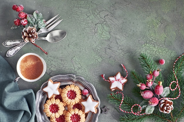 Flat lay with xmas decorations in green and red with frosted berries and trinkets, coffee and christmas cookies