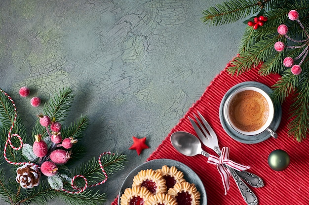 Flat lay with xmas decorations in green and red with frosted berries and trinkets