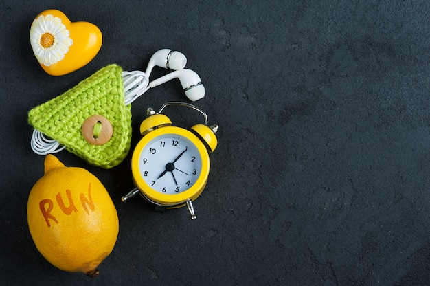 Flat lay with yellow alarm clock and lemon on black background