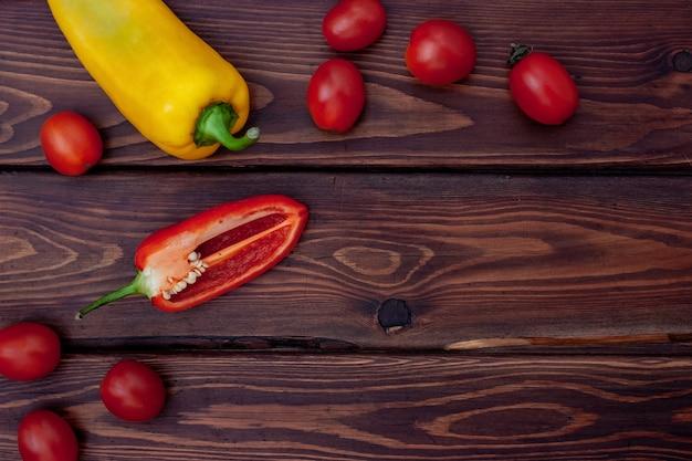 Плоская кладка с желтым перцем и нарезанным красным перцем с небольшими помидорами на коричневых досках