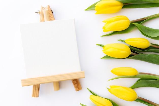 黄色いチューリップの花と白い背景の上の空の額縁でフラットレイ。