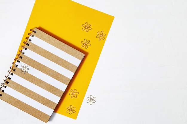 Flat lay withgold melal clips, fashion copybook for writing and drawing on tabletop work space with copy space. top view.